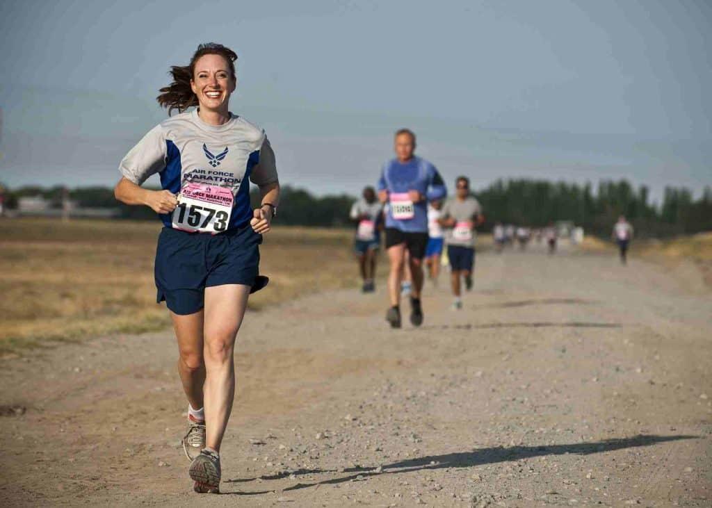 Kobieta biegnąca po nieutwardzonej drodze