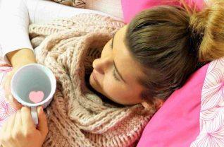 Kobieta w łóżku trzymająca kubek z napojem