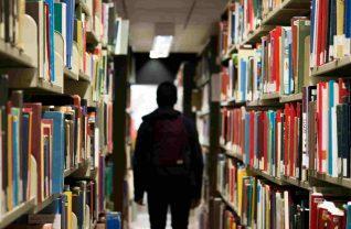 Student w bibliotece między regałami