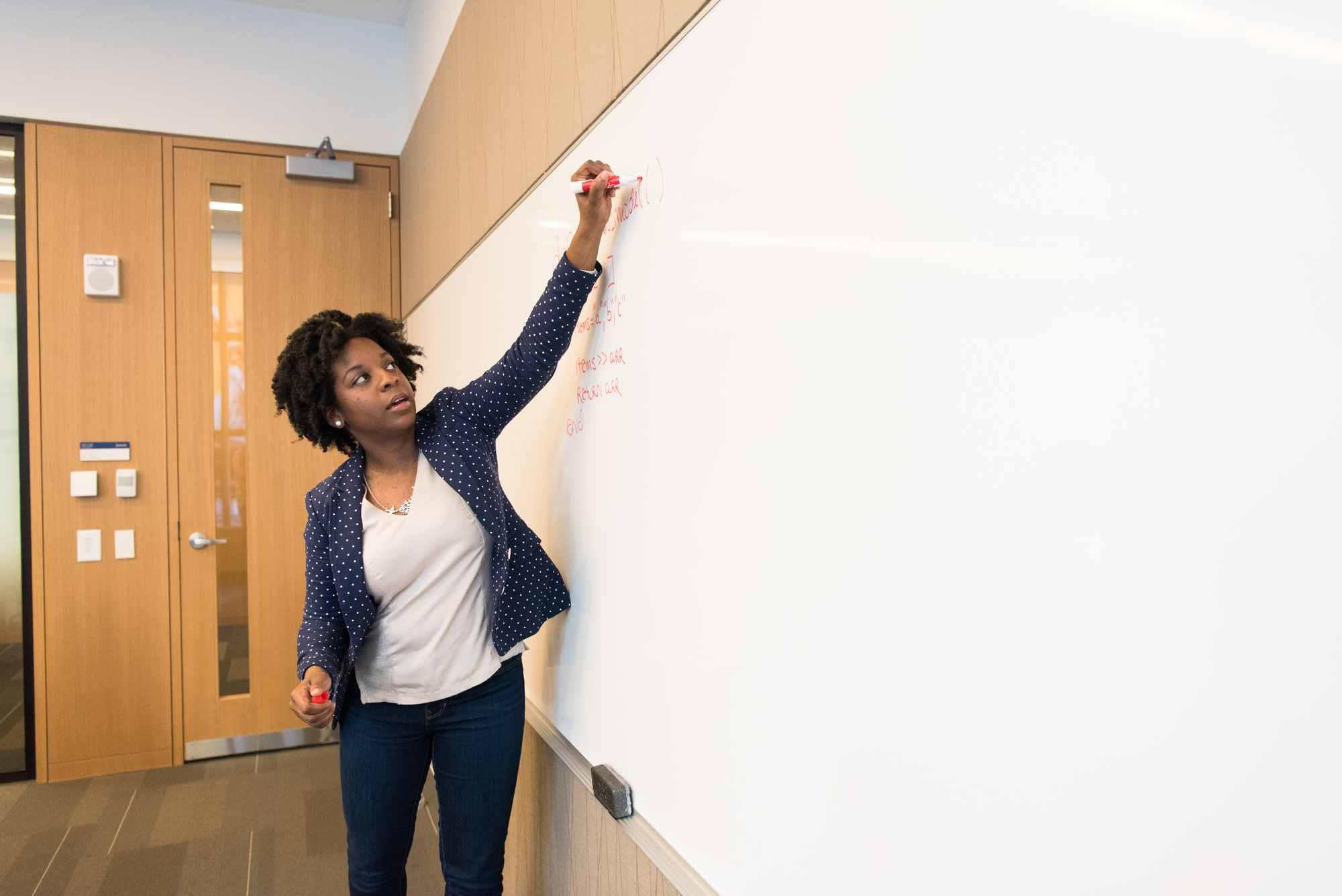 Nauczycielka pisząca na tablicy szkolnej