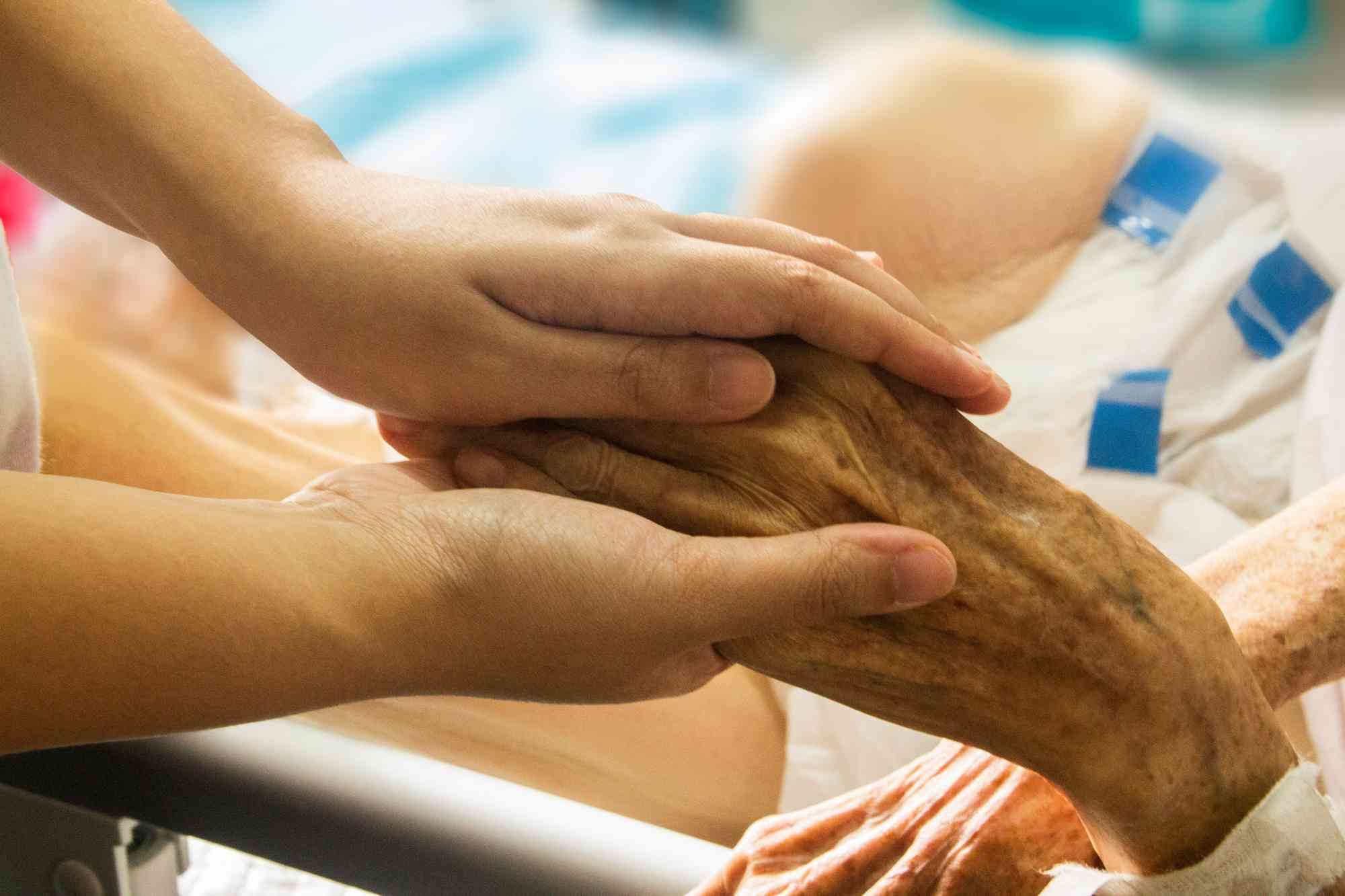 Osoba trzymająca rękę pacjenta w szpitalu