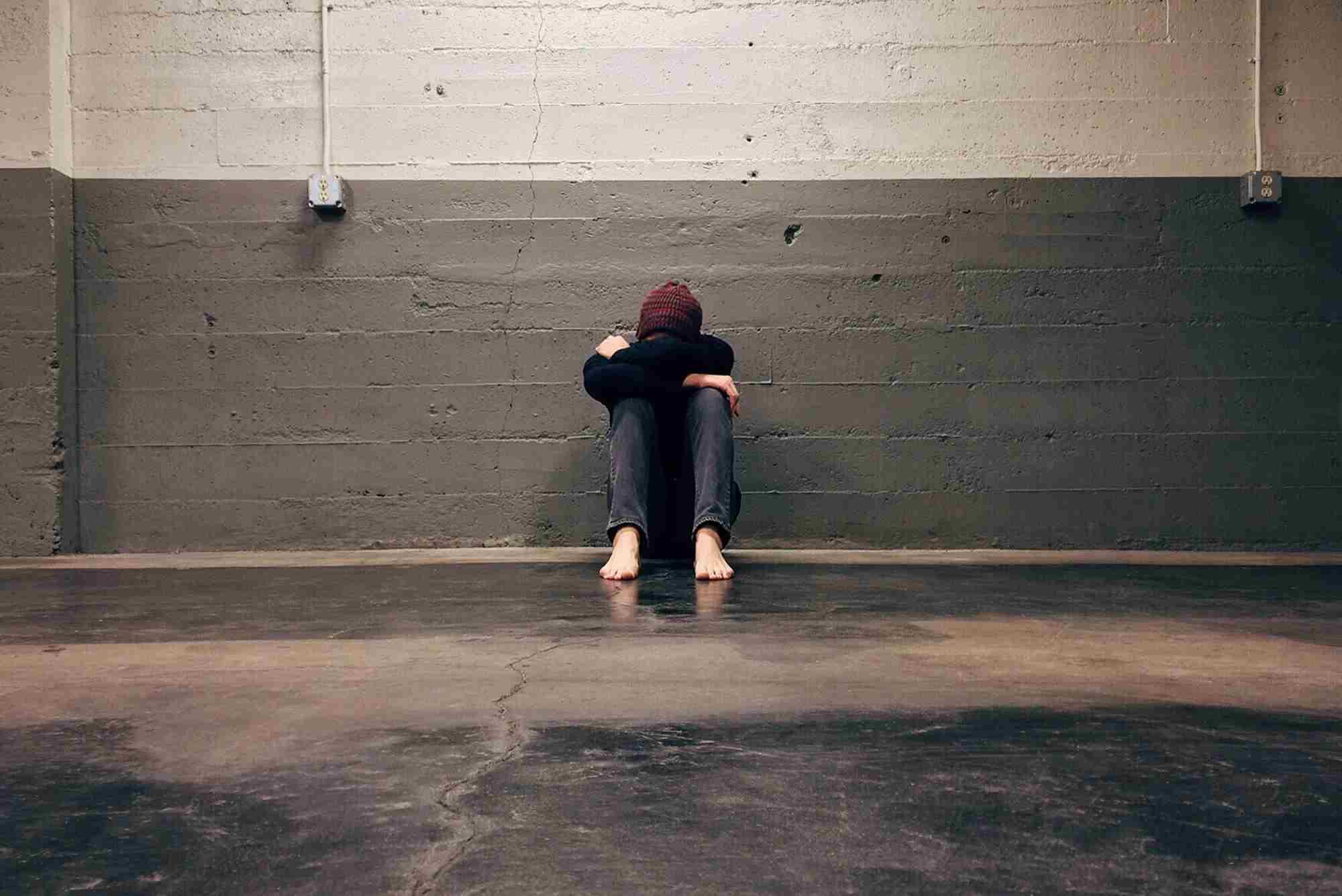 Mężczyzna w kapturze siedzący przy ścianie