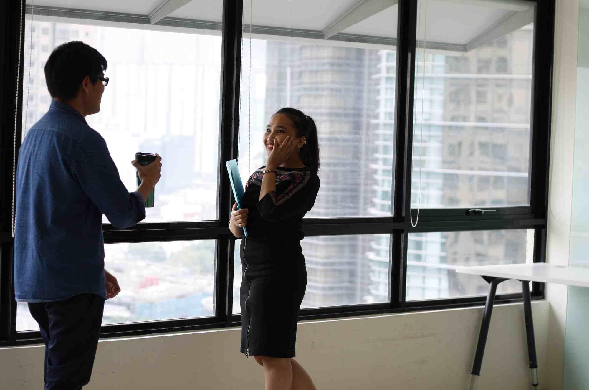 KObieta w zcarnym kostiumie rozmawiająca z mężczyzną w biurze