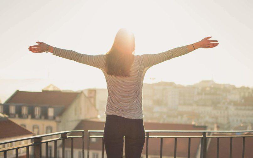 KObieta na balkonie o wschodzie słońca