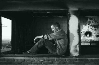 Czarno białe zdjęcie mężczyzny siedzącego tyłem do ściany