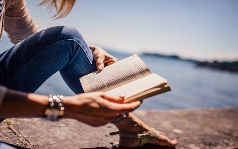 Kobieta czytająca książkę nad morzem