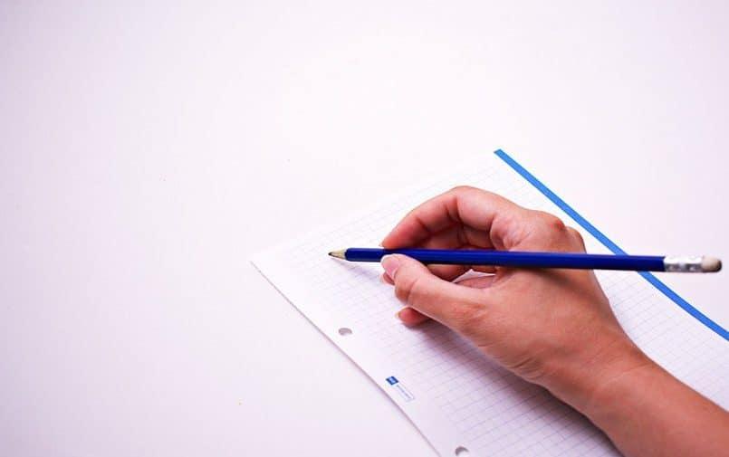 Ręka trzymająca ołówek na tle kartki papieru