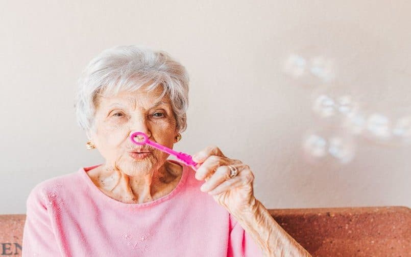 Starsza kobieta robiąca bańki mydlane