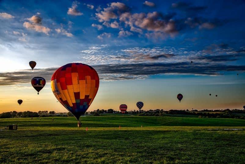 Kolorowe balony wylatujące w powietrze nad polem