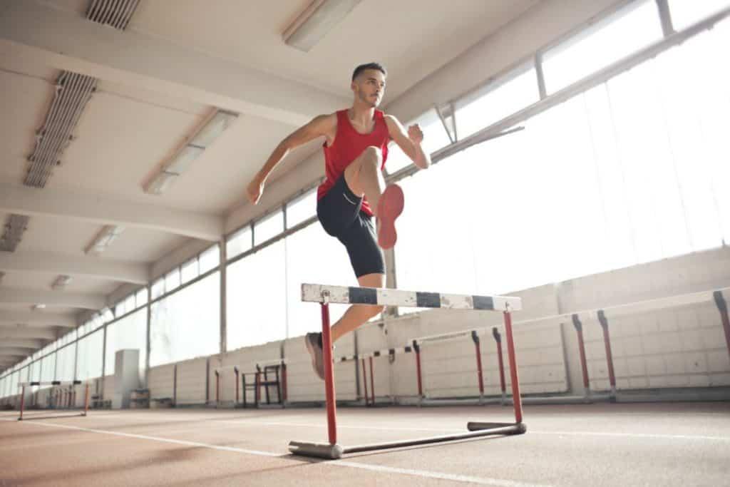 Sportowiec skaczący przez przeszkody