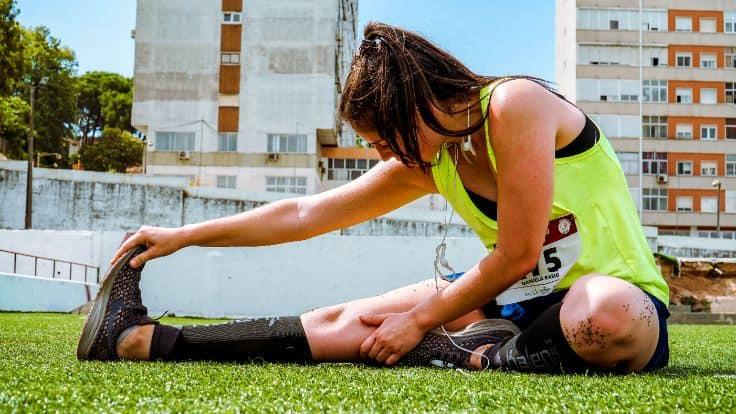 Kobieta w sportowych ubraniach rozciągająca się na trawniku