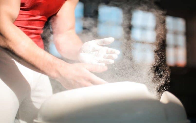 Sportowiec pokrywający dłonie magnezją
