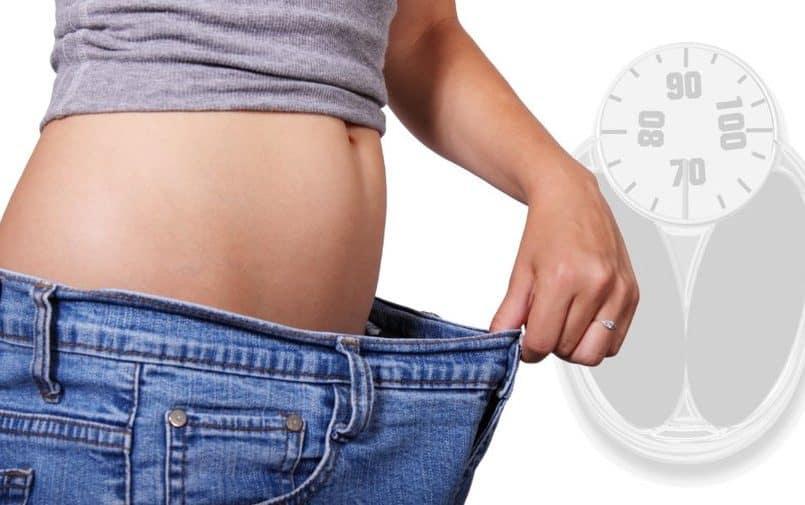 Kobieta trzymająca za duże spodnie jeansowe