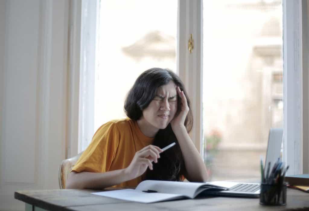 Studentka siedząca przy biurku z grymasem na twarzy