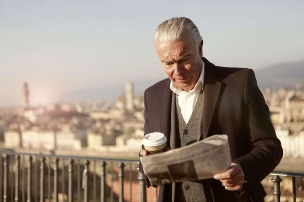 Starszy mężczyzna w garniturze czytający gazetę