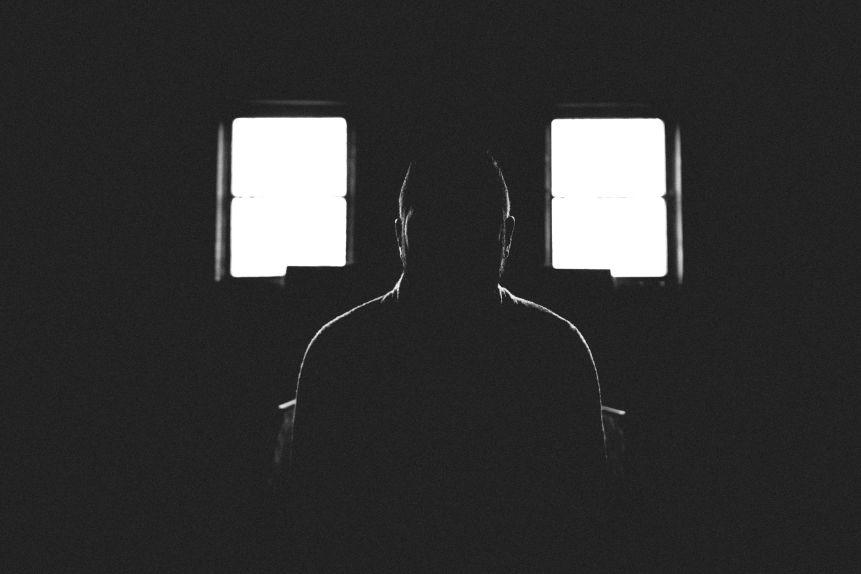 Mężczyzna siedzący w ciemnym pokoju
