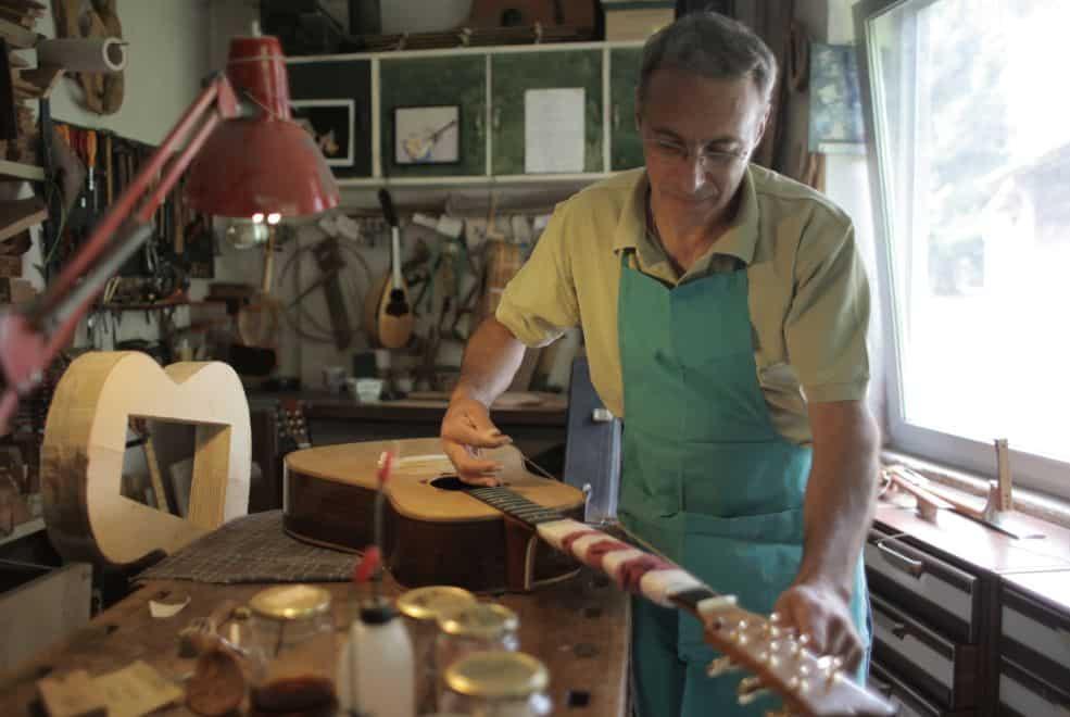 Senior naprawiający gitarę w swoim warsztacie