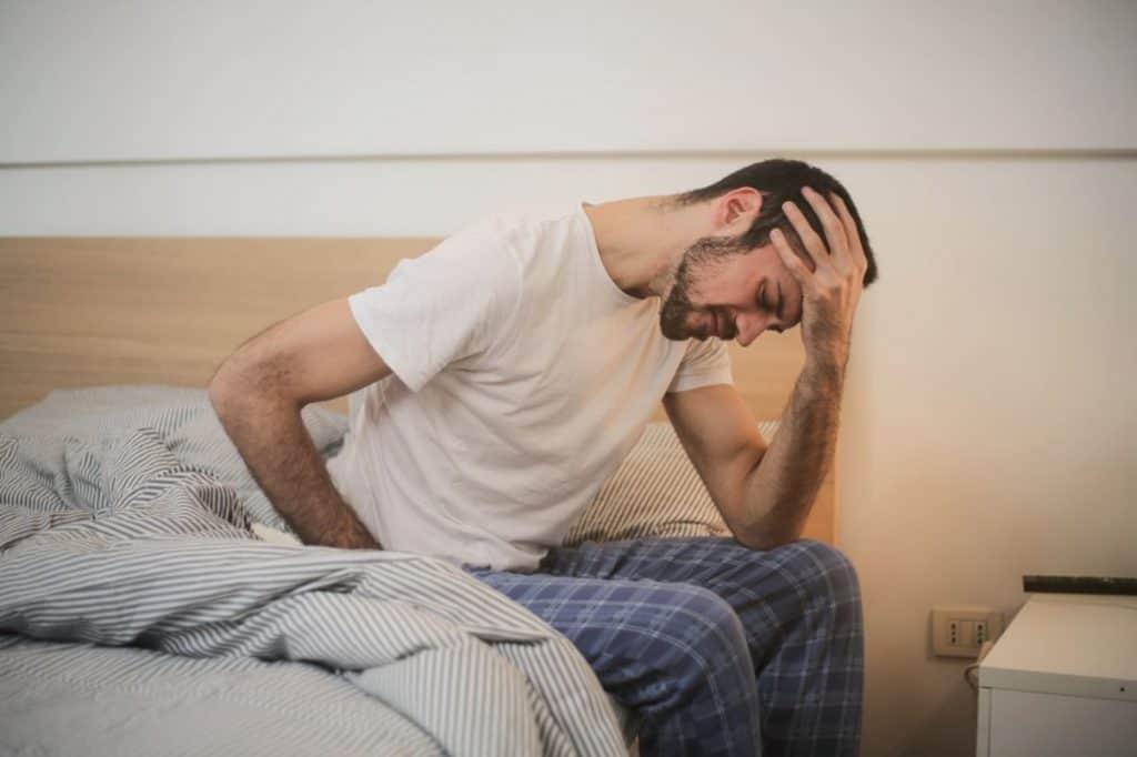 Młody mężczyzna w piżami siedzący na łóżku z dłonią na czole