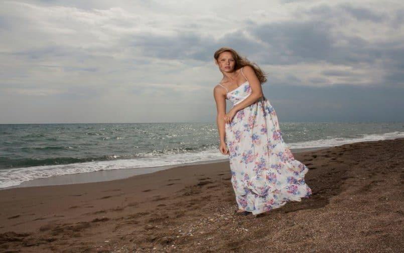 Blondynka w kwiecistej sukience nad brzegiem morza