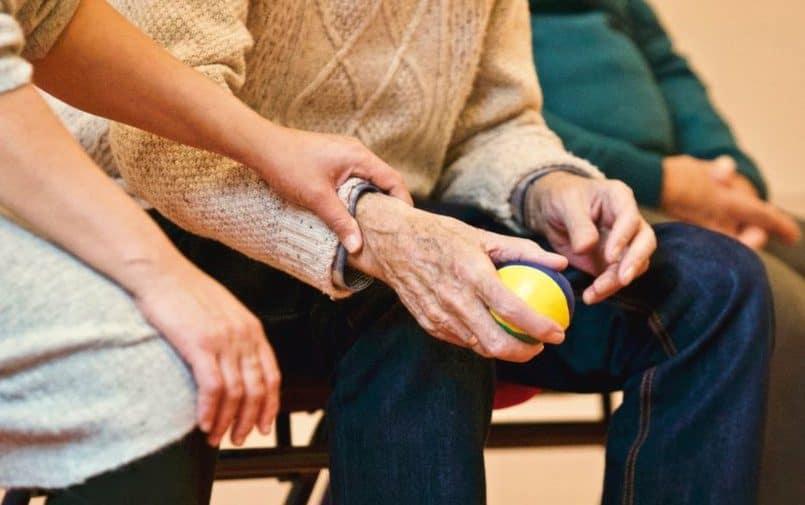 Starsza osoba trzymająca piłeczkę
