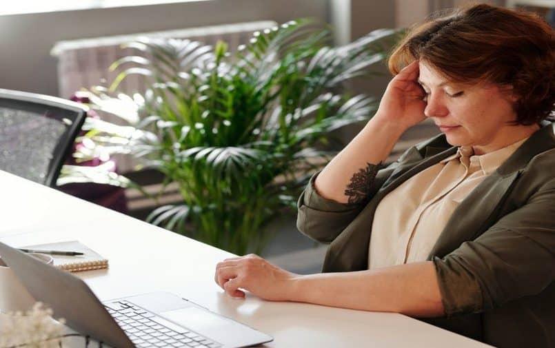 Kobieta przy biurku trzymająca się za głowę
