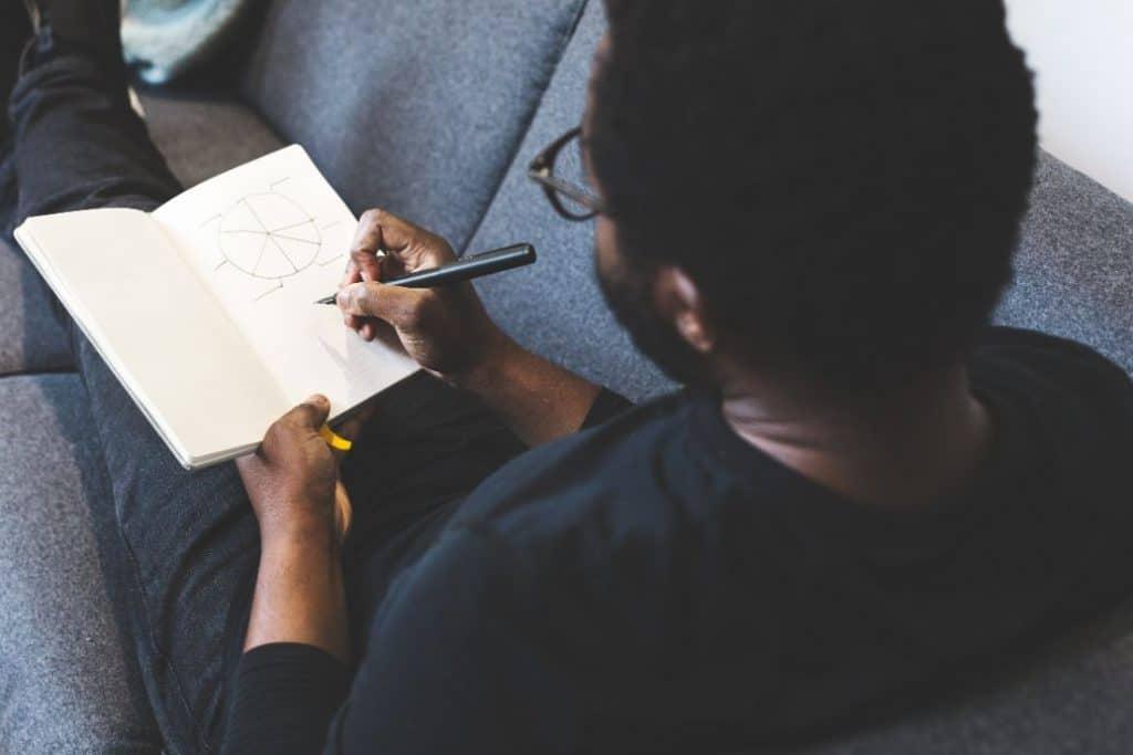 Czarny mężczyzna na kanapie piszący w notatniku