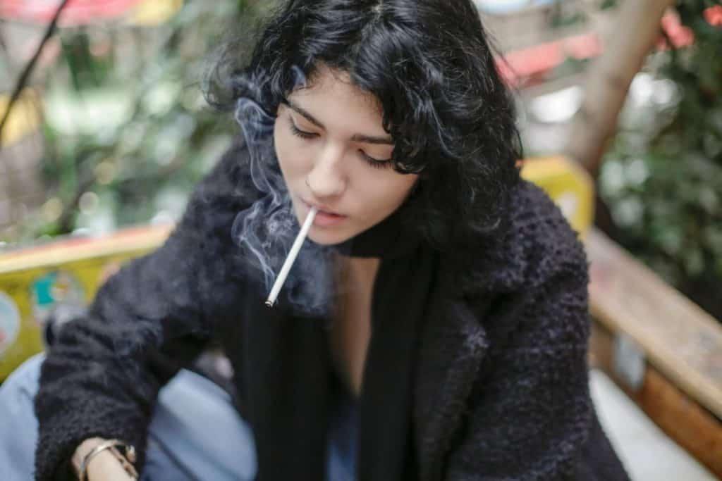 Ciemnowłosa kobieta paląca papierosa