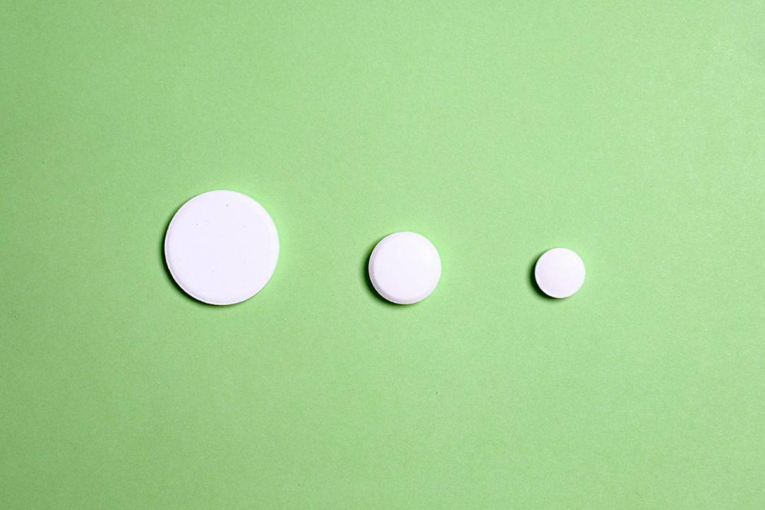 Białe tabletki na zielonym tle