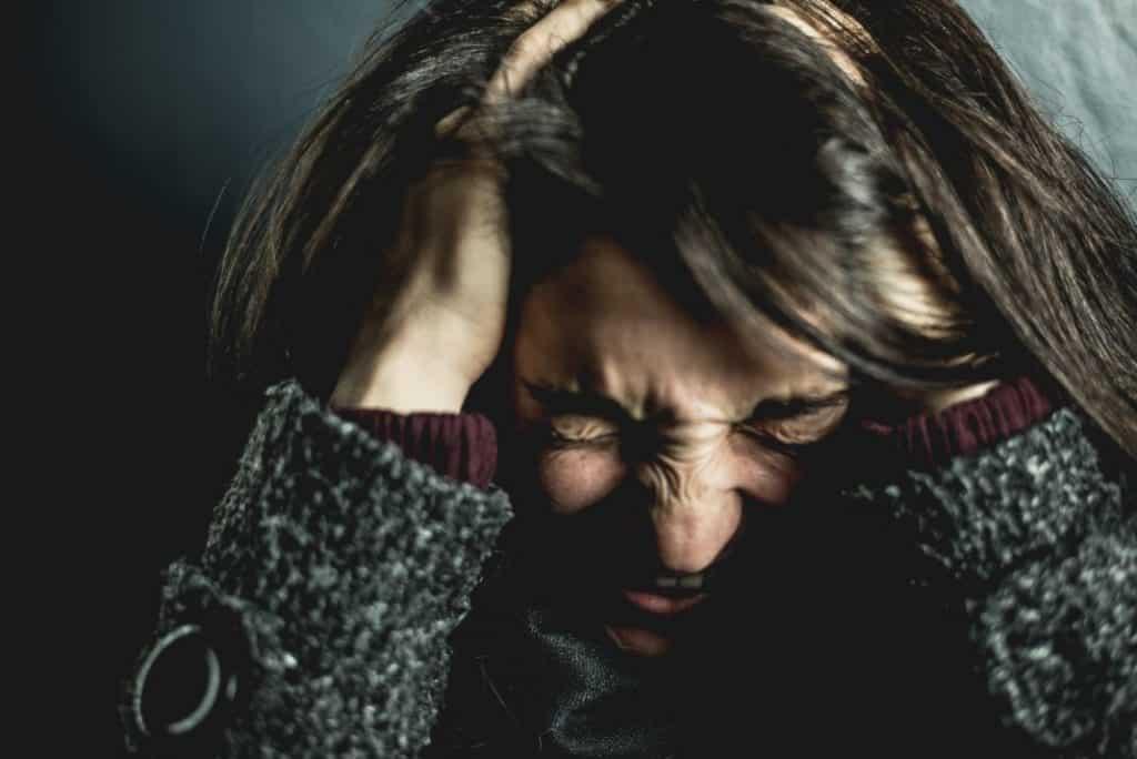 Zestresowana kobieta trzymająca się za głowę