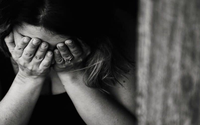 Płacząca kobieta z twarzą w dłoniach