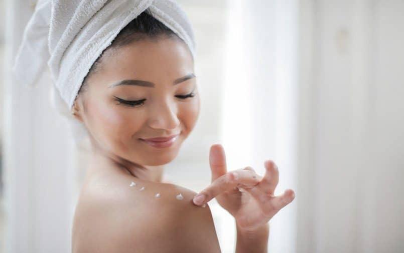 Kobieta w ręczniku na głowie nakładająca balsam