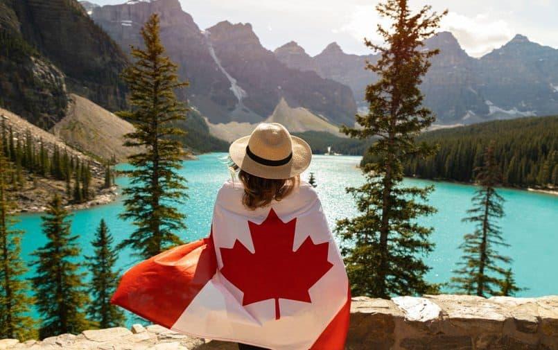 Kobita siedząca w górach owinięta flagą kanadyjską