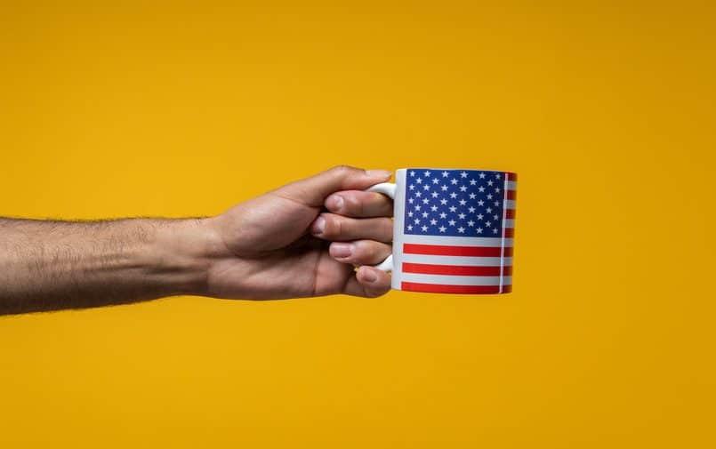 Osoba trzymająca kubek z flagą USA