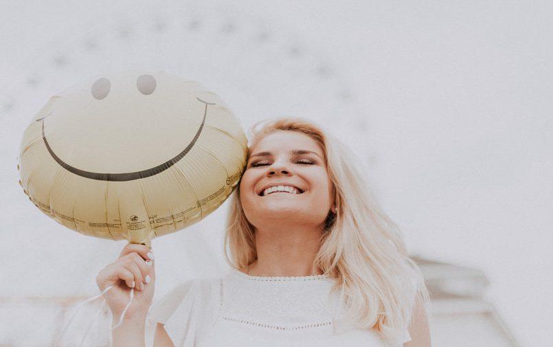 Szczęśliwa kobieta z balonikiem w ręce