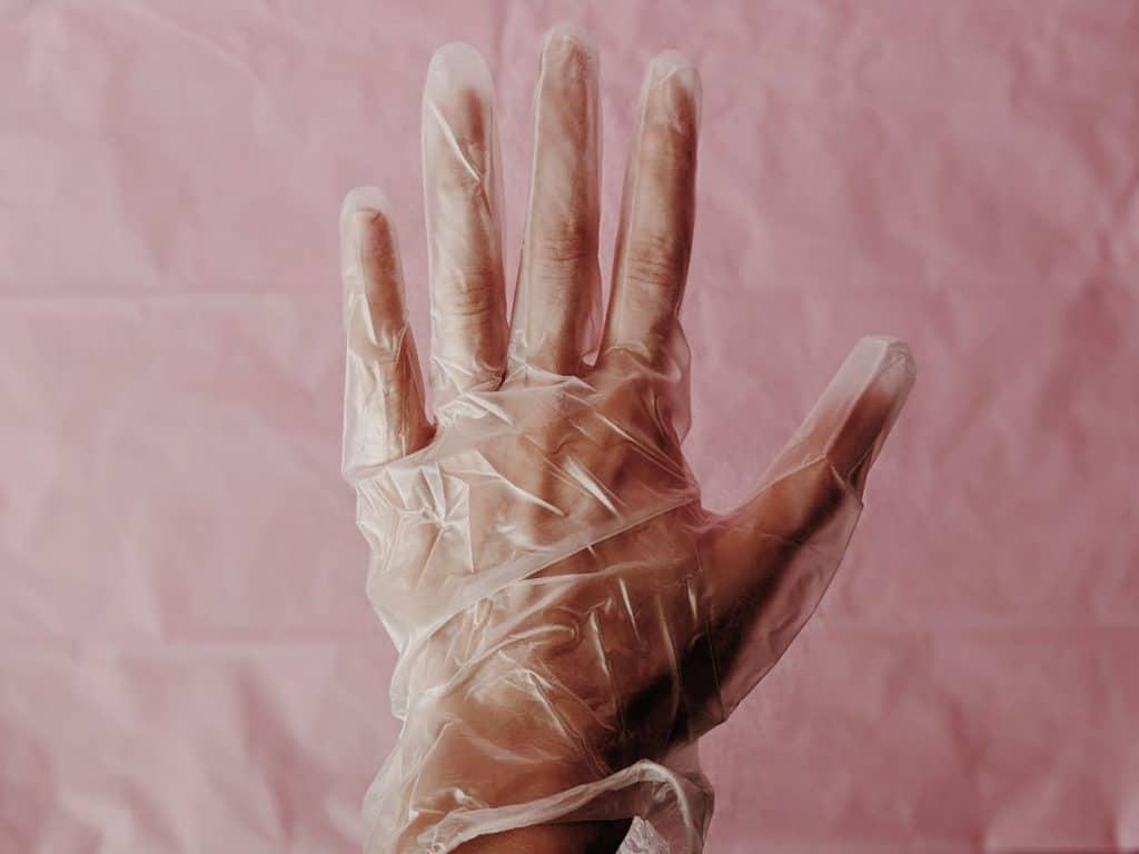 Dłoń w jednorazowej rękawiczce