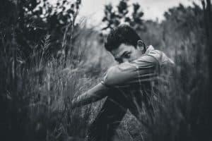 Biało-czarne zdjęcie mężczyzny siedzącego w trawie