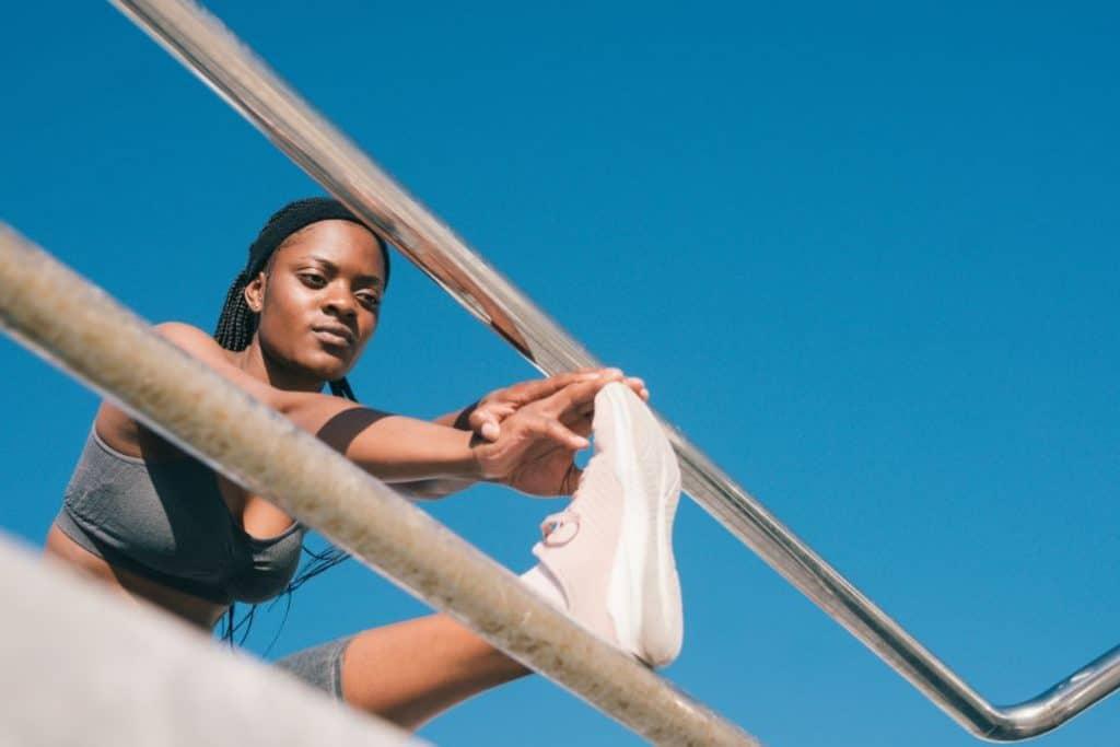 Czarna kobieta rozciągająca się przy barierce