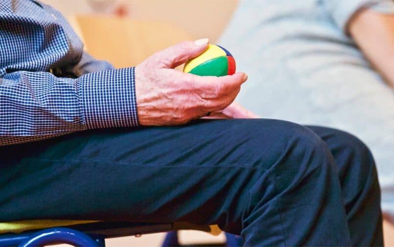 Starszy mężczyzna trzymający piłeczkę w ręku