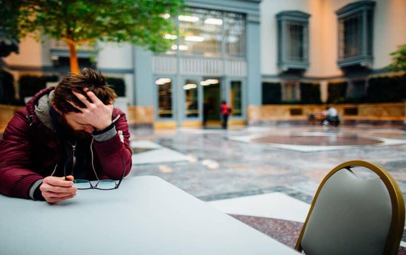 Mężczyzna siedzący przy stole i trzymający się za głowę