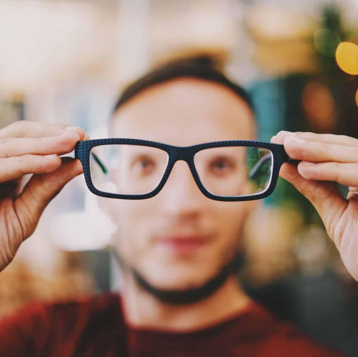 Mężczyzna trzymający okulary