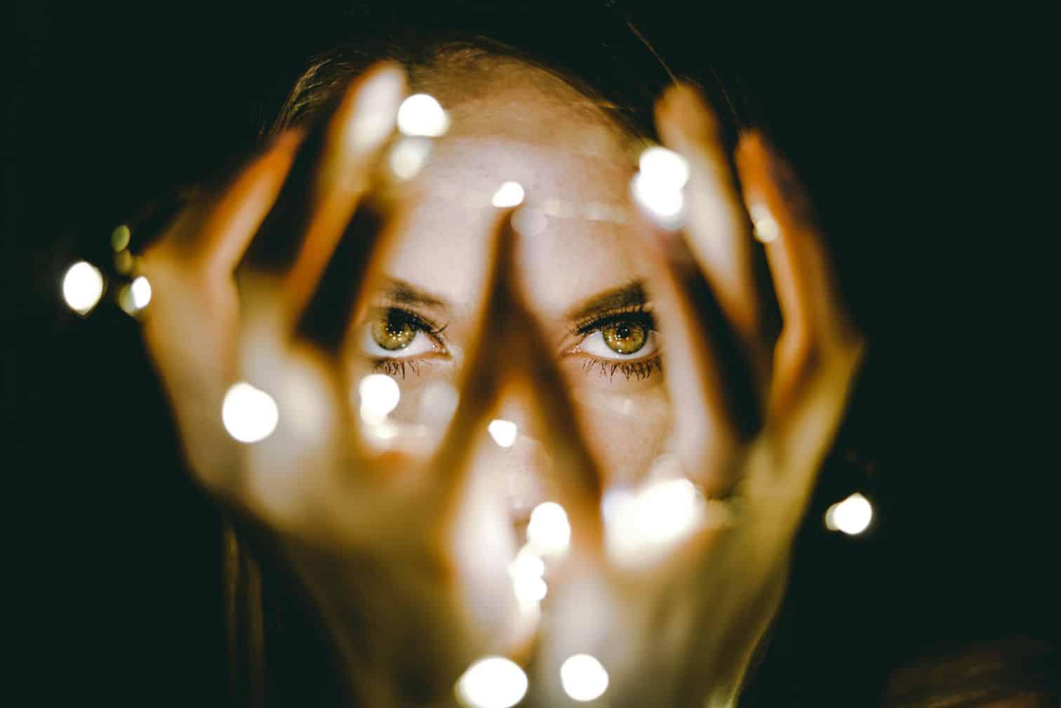 Kobieca twarz oświetlona lampkami