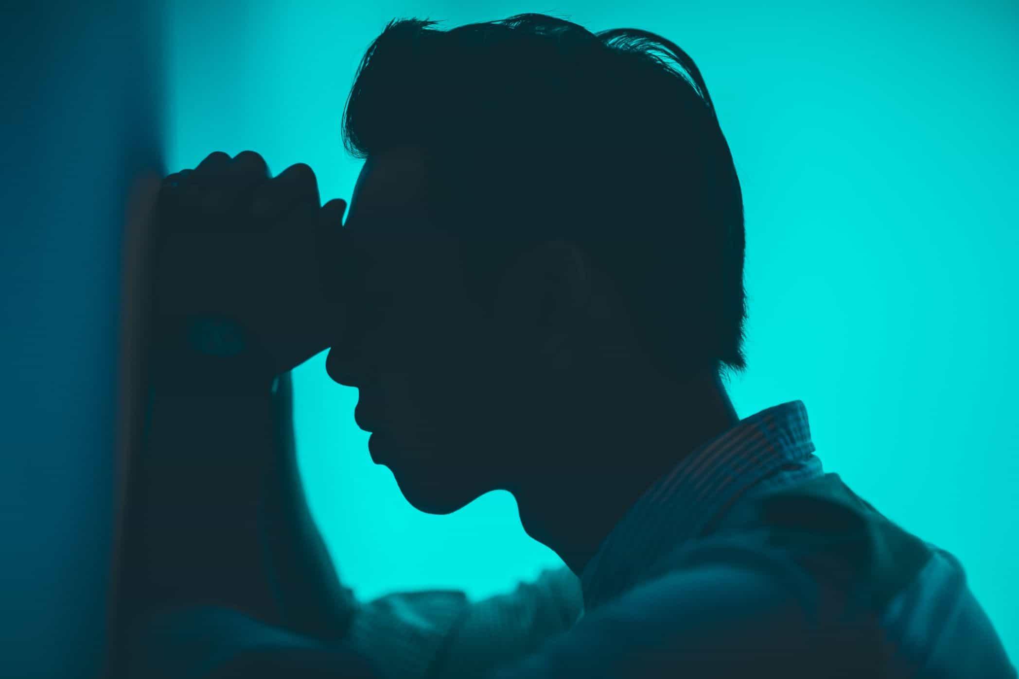 Mężczyzna opierający głowę o ścianę