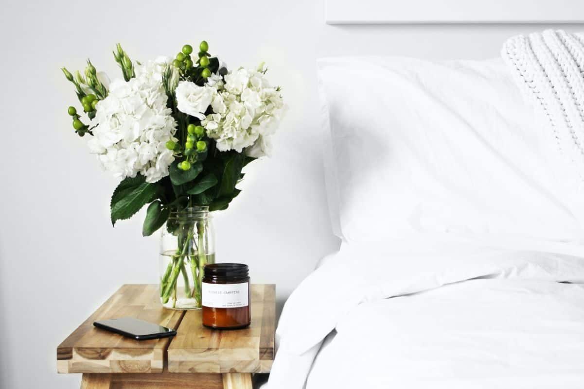 Pościelone łóżko i kwiaty