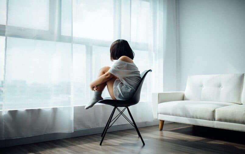Dziewczyna na krześle patrząca w okno